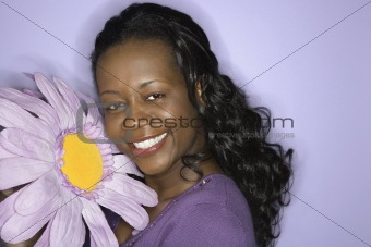 African-American woman holding oversized flower.