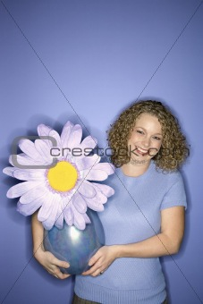Caucasian woman holding oversized fake flower in vase.
