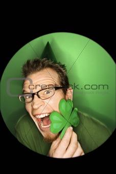Caucasian man holding shamrock.