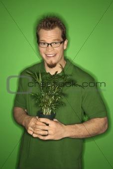 Caucasian man holding plant.