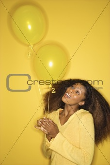 Young African-American woman holding balloons.
