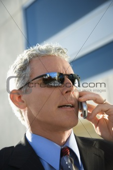 Businessman talking on cellphone in urban setting.