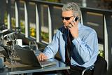 Businessman looking at laptop and talking on cellphone.