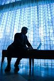 Businessman sitting on bench typing on laptop.