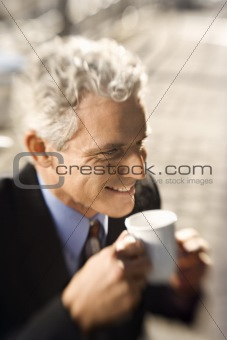 Businessman drinking coffee and smiling.