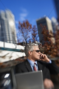 Businessman sitting  outside talking on cellphone with buildings