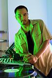 Male DJ leaning on turntable.