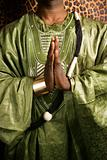 Man in traditional African clothing with hands together.