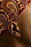 Close-up of man's ear and African hat.