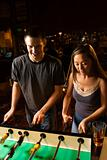 Young couple playing foosball table.