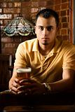 Young man holding beer.