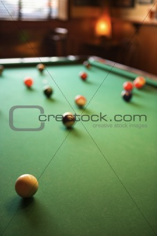 Green billiards table with pool balls spread out.