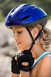 Young woman putting on bicycle helmet.