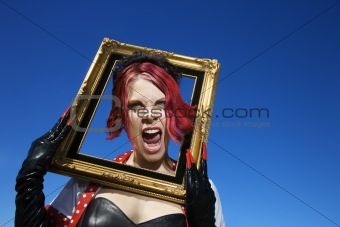 Adult female holding empty frame around face.