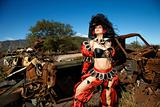 Woman dressed as pirate in junkyard.
