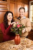 Man and woman arranging flowers.