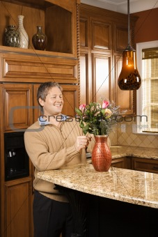 Male arranging flowers in vase.