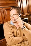 MId-adult male talking on cellphone in kitchen.