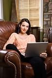 Woman sitting in chair with laptop.