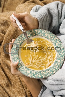 Bowl of chicken noodle soup held in hands.