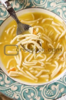 Bowl of chicken noodle soup with spoon.