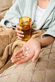 Woman holding pills and glass of water.