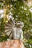 Low angle of stone gargoyle statue outdoors.