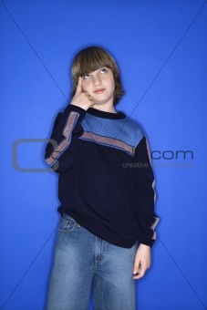 Caucasian boy pointing at his head.