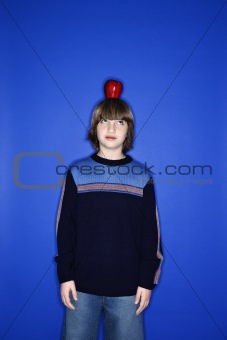 Caucasian boy with an apple on his head.