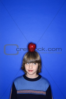 Caucasian boy with apple on his head.
