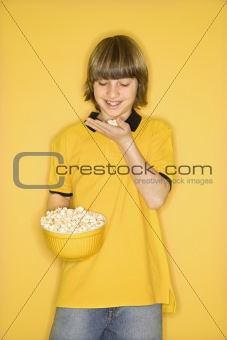 Caucasian boy with bowl of popcorn.