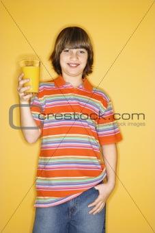 Caucasian boy holding glass of orange juice.