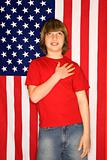 Caucasian boy with hand over heart with american flag background