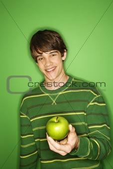 Caucasian teen boy holding apple.
