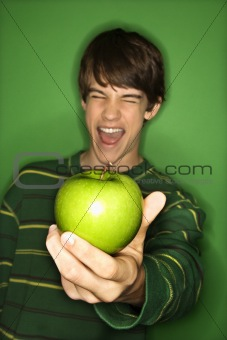 Caucasian teen boy holding apple.