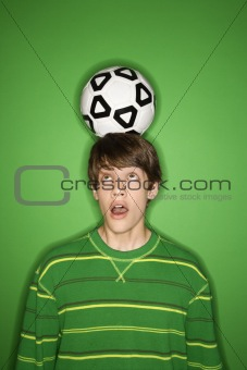 Caucasian teen boy with soccer ball on head.