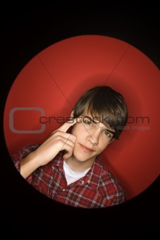 Caucasian teen boy pointing to his head.