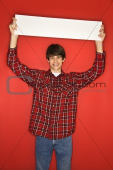 Caucasian teen boy holding blank sign above his head.