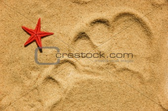 Toes trace on sand and red star