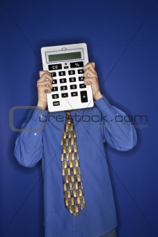 Caucasian teen boy holding big calculator.
