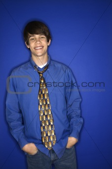 Caucasian teen boy with hands in pockets.