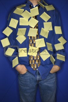 Caucasian teen boy covered with sticky notes.