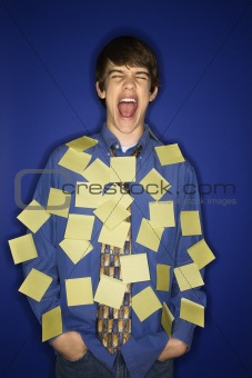 Caucasian teen boy covered with sticky notes screaming.