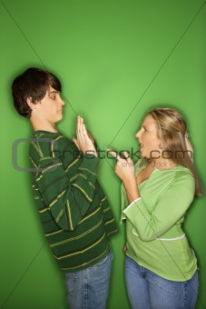 Caucasian teen boy and girl fighting.