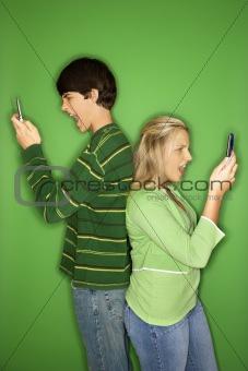 Caucasian teen boy and girl on cellphones.
