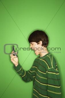 Caucasian teen boy screaming at cellphone.
