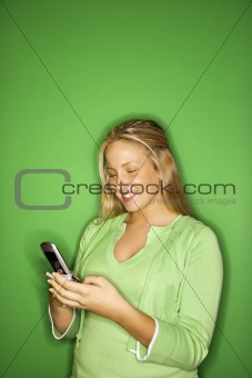 Caucasian teen girl smiling at cellphone.