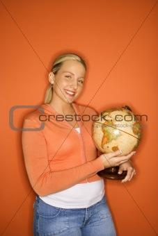 Caucasian teen girl holding globe.