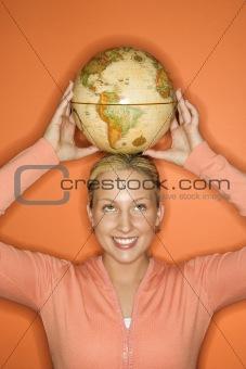 Caucasian teen girl holding globe on head.