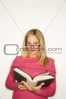 Caucasian teen girl holding book.